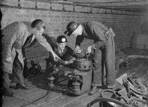 Classic British workwear clothing,1944 photo of Men in work clothing at the British Training School Sheffield, West Riding, Yorkshire, England, UK, using American Mining Equipment,