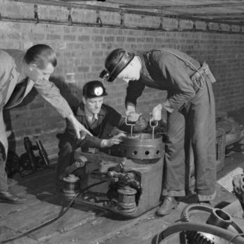 Classic British workwear clothing,1944 photo of Men in work clothing at the British Training School Sheffield, West Riding, Yorkshire, England, UK, using American Mining Equipment,