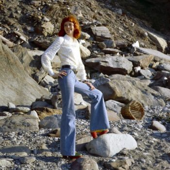 Vintage clothing online- Rehead model in white blouse and bell bottom jeans, Devon, UK, 1970s.