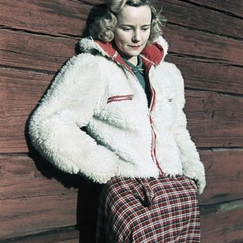 The 40s fashion, Woman wearing white fleece jacket and checked skirt leaning against wall, Photo by Gunnar Lundh. 1941