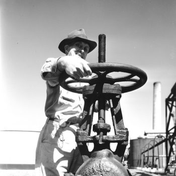 vintage workwear clothing-Worker operating oil pipeline valve, Texaco, TX, USA, 1944.