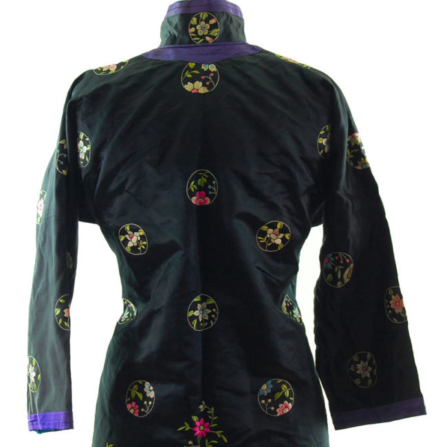 close back Features a black block colour shirt with embroidered flowers and hills on the hemline with embroidered flowers.