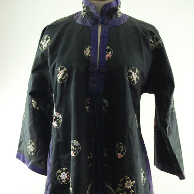 close up of Features a black block colour shirt with embroidered flowers and hills on the hemline with embroidered flowers.