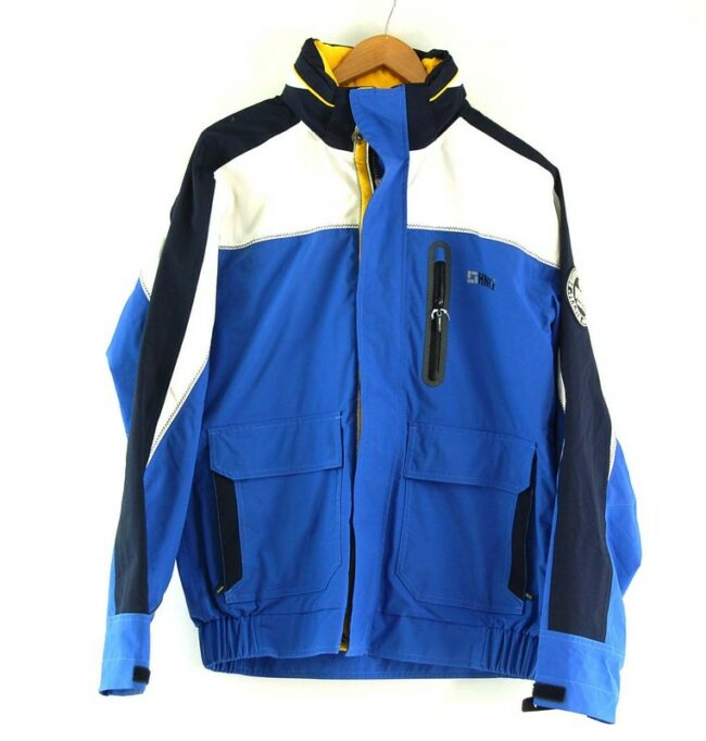Human Nature Waterproof Jacket. Features a blue body with white and dark blue panels, 'HN97' logo at right side chest and 'HN 97 Nautical' patch on right sleeve and two large front patch pockets. Has front zip opening with popper flap, a funnel collar with fold away hood, cuffs with velcro straps and an elastciated waitband. Fully lined with one inner pocket. Size medium.